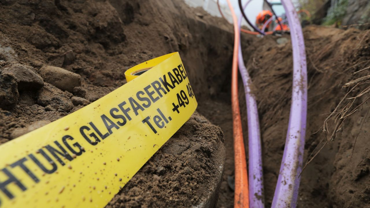 """Drei verschiedenfarbige Kabel werden gerade in die Erde verlegt. Neben den Kabeln liegt ein Band mit der Aufschrift: """"Achtung Glasfaserkabel"""" und einer Telefonnummer."""