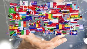 Eine Hand hält symbolisch die Flaggen der Länder der Welt