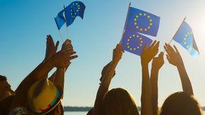 Jugendliche am Strand. In den Händen halten sie kleine Europa-Fahnen