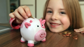 Ein Mädchen steckt eine Münze in ein Sparschwein
