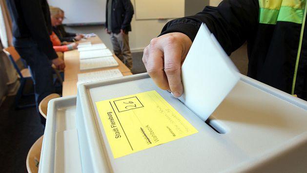 Eine Hand steckt einen Zettel in den Schlitz einer Wahlurne.