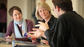Eine Frau im Gespräch mit zwei Beratern.