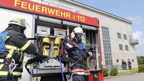 Feuerwehrleute ziehen ihre Schutzkleidung an.