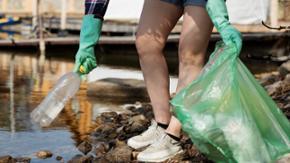 Eine junge Frau hebt eine Plastikflasche aus dem Wasser, um sie in einen Plastik-Müllsack zu werfen.