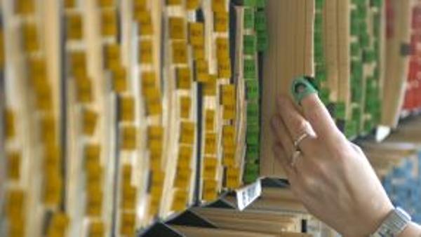 Ein Hand zieht eine Akte aus einer Registratur