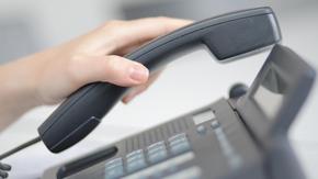 Nahaufnahme einer Hand, die einen Telefonhörer hält.