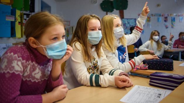 Eine Schülerin hebt im Unterricht  die Hand. Neben ihr sitzen zwei weitere Mädchen, alle tragen eine medizinische Maske.