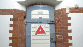 Eine Gefängnistür mit dem Symbol der Agentur für Arbeit