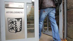 """Ein Mann geht durch eine Tür mit der Aufschrift """"Justizvollzugsanstalt"""""""