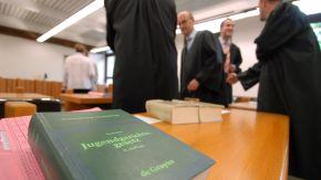 Im Vordergrund ein Gesetzbuch, im Hintergrund mehrere Anwälte im Gespräch