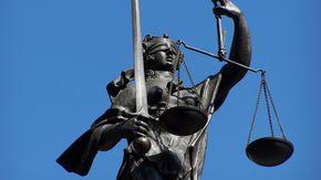 Eine Statue hält mit verbundenen Augen eine Waage