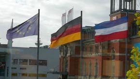 Vor dem Kieler Hauptbahnhof wehen viele Flaggen, zu sehen sind die Flaggen Europas, Deutschlands und Schleswig-Holstein