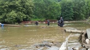 Polizeitaucher suchen einen Abschnitt im Hochwassergebiet in Rheinland-Pfalz ab.