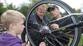Zwei Männer stehen hinter einem Fahrrad und reparieren einen Reifen. Ein Junge schaut interessant zu.