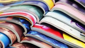mehrere Zeitschriften liegen aufgeschlagen übereinander