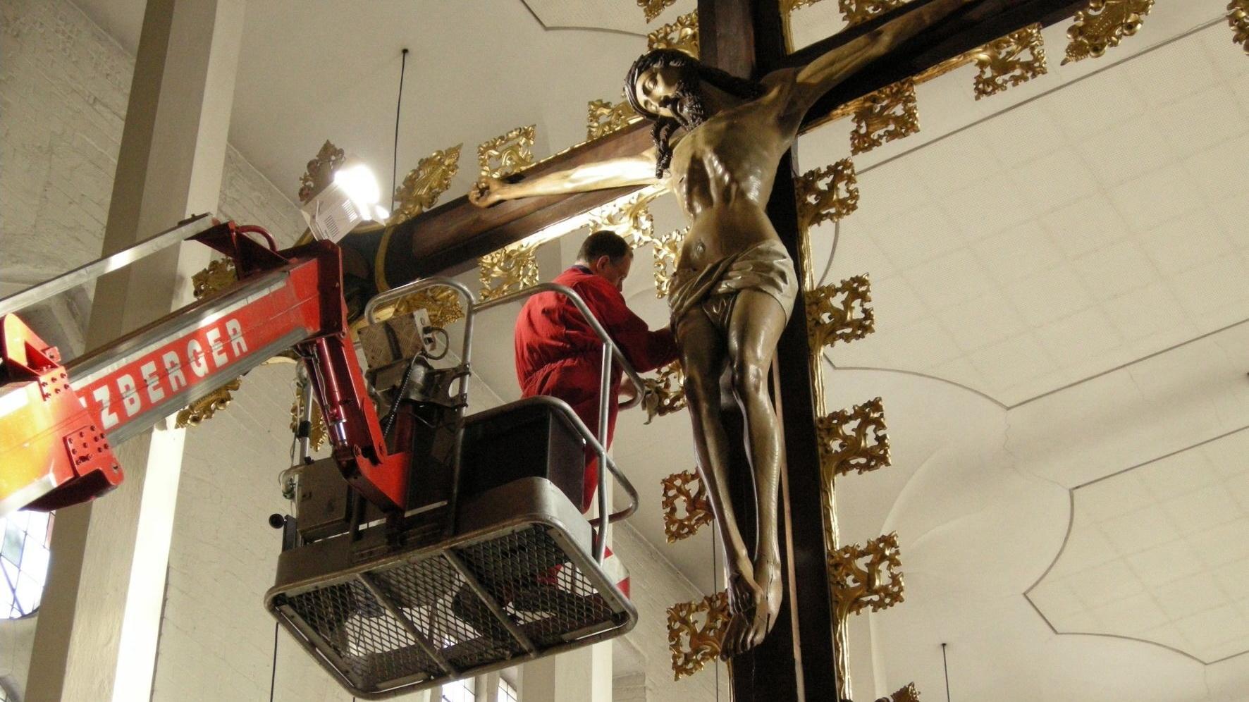 Reinigungsarbeiten von einem Hubwagen aus am Kruzifix in der Kieler Nikolaikirche