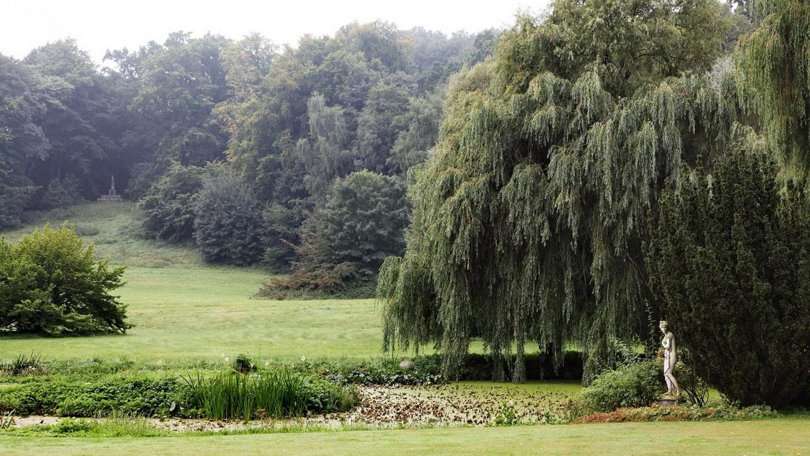 Blick in den Park auf Gut Panke rmit Baumgruppen und kleiner Statue