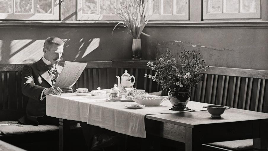 Fotograf Theodor Möller, Zeitung lesend in seiner Wohnstube mit Kaffeetafel.
