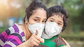 Mutter und Kind tragen Mundschutz zur Corona-Prävention