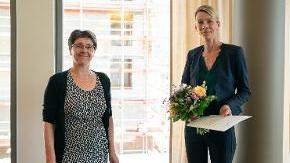 Finanzministerin Monika Heinold und Dr. Silke Torp mit einem Blumenstrauß lächeln nach der Ernennung