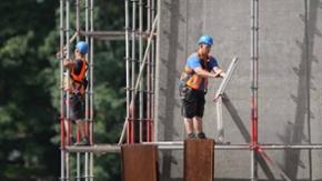 Arbeiter auf einem Gerüst an einem Gebäude