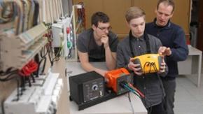 Ein Mann erklärt zwei weiteren etwas an einem elektrischen Messgerät