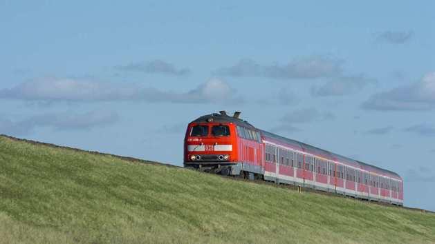 Roter Zug auf grasbewachsenem Damm vor blauem Himmel