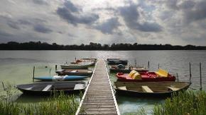 Holzsteg mit Booten ragt in einen See, Wolken mit Sonnenlicht