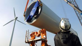 Ein Bauarbeiter blickt hoch zu einem riesigen Bauteil für eine Windkraftanlage. A worker looking at a large part of a wind engine.